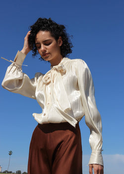 Maya wears the Celeste Gathered Pussy-bow Blouse in Marzipan from Laundromat