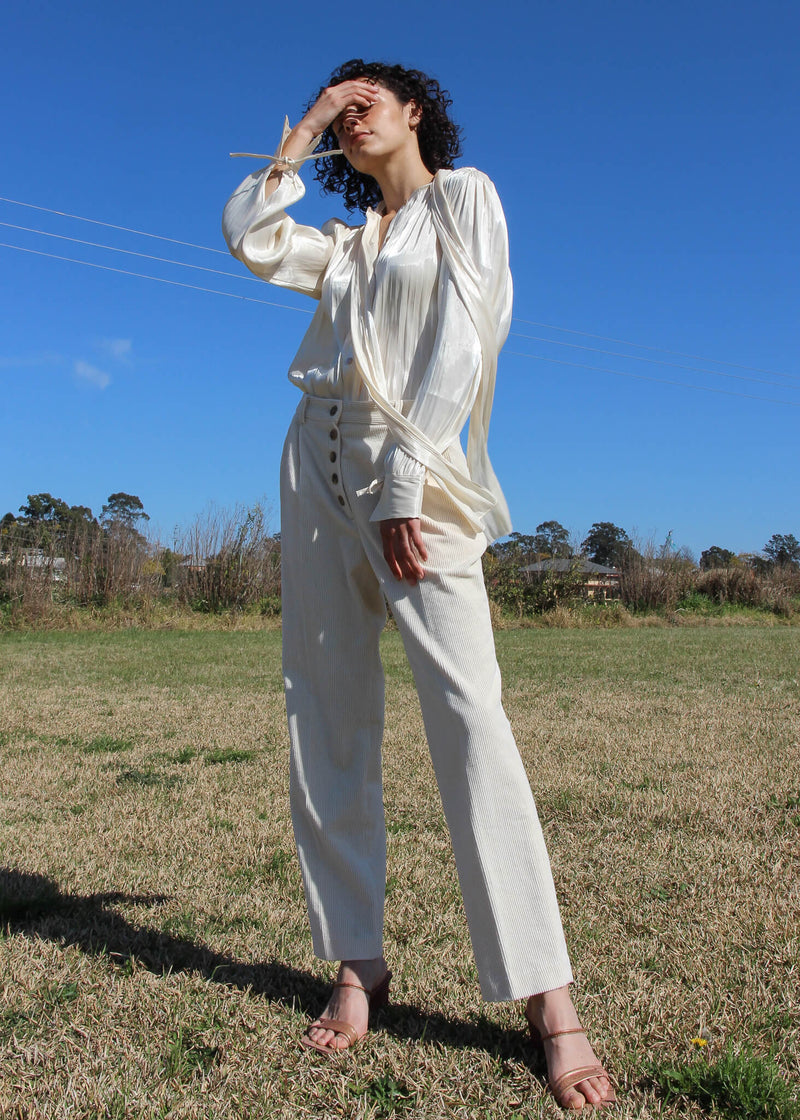 Maya wearing the Celeste Gathered Pussy-bow Blouse and corduroy trousers, both from Laundromat