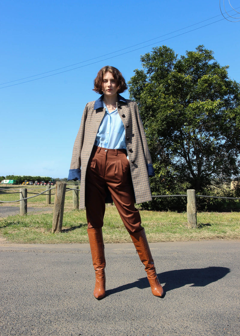 Olivia wears the Daria Wool Pleat Trousers with wool coat, both from Laundromat
