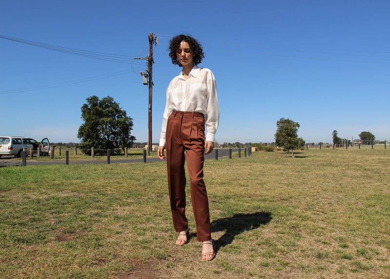 Maya wears the Daria Wool Pleat Trousers in a grassy field