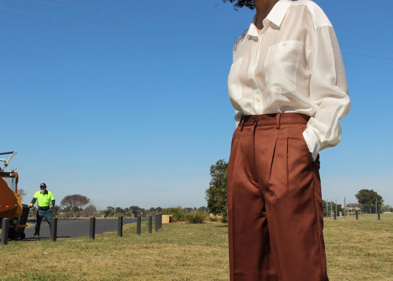 Detail of the Daria Wool Pleat Trousers with white shirt, both by Laundromat