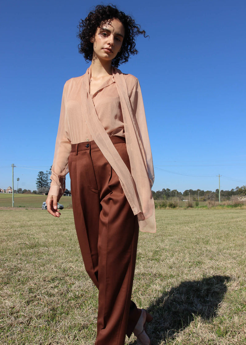 Maya wearing the Daria Wool Pleat Trousers in Walnut from Laundromat