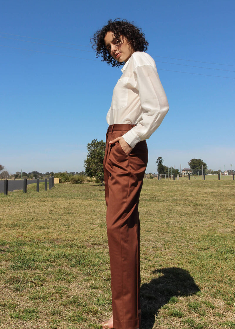 Maya with hands in the pockets of the Daria Wool Pleat Trousers in Walnut