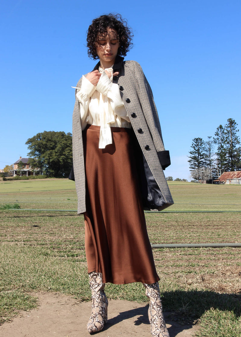 Maya wearing the Edie Wool Car Coat over a blouse and skirt, all from Laundromat
