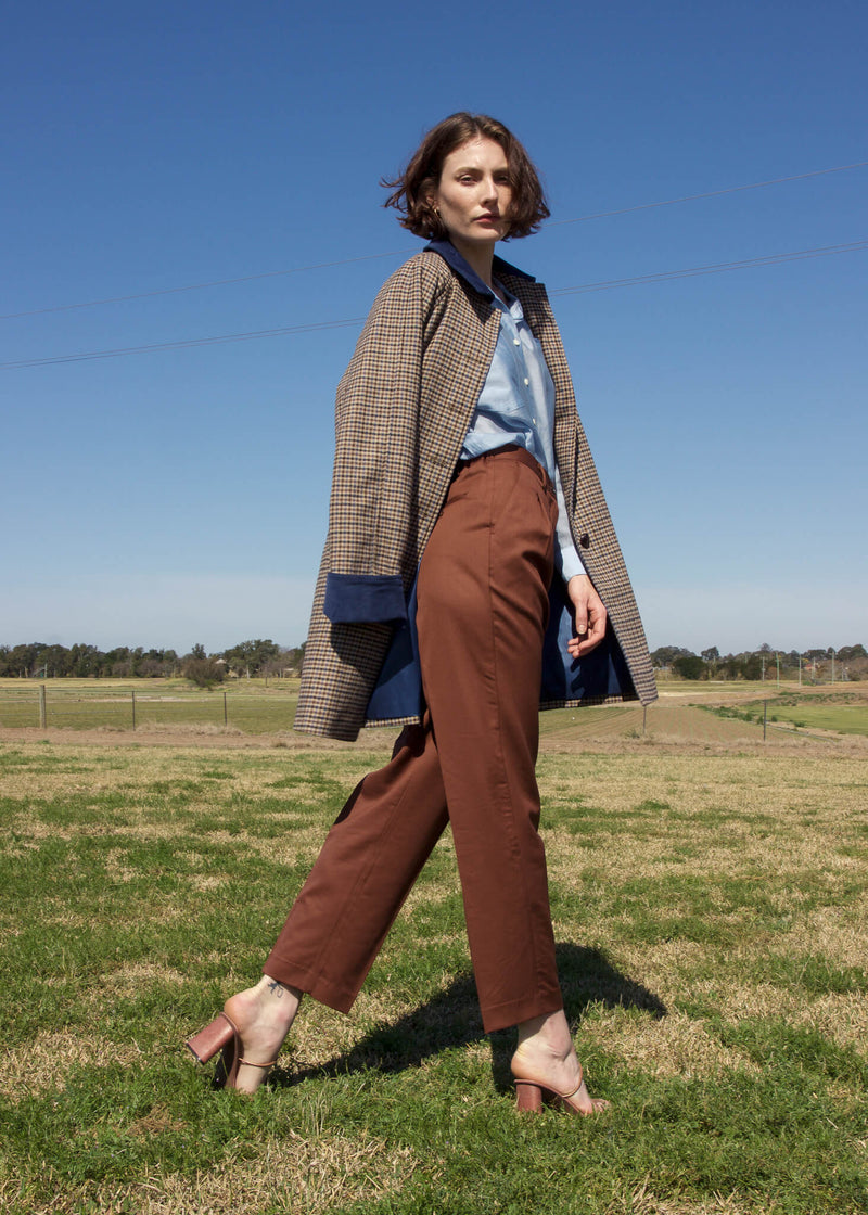 Olivia wears the Edie Wool Car Coat with wool trousers, both from Laundromat