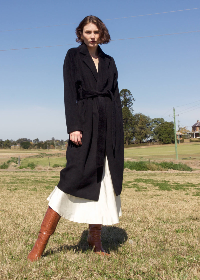 Olivia wears the Kasia Llama Wool Coat with white skirt, both from Laundromat