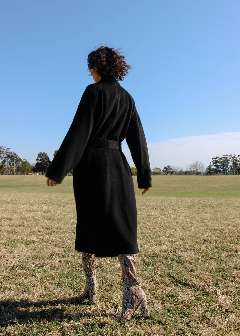Back of Maya wearing the Kasia Llama Wool Coat from Laundromat