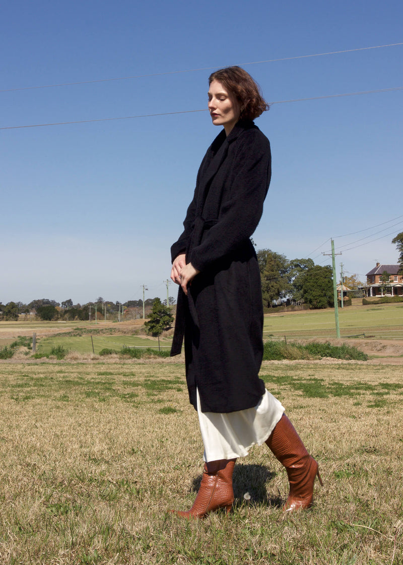 Olivia wearing the Kasia Llama Wool Coat and skirt from Laundromat