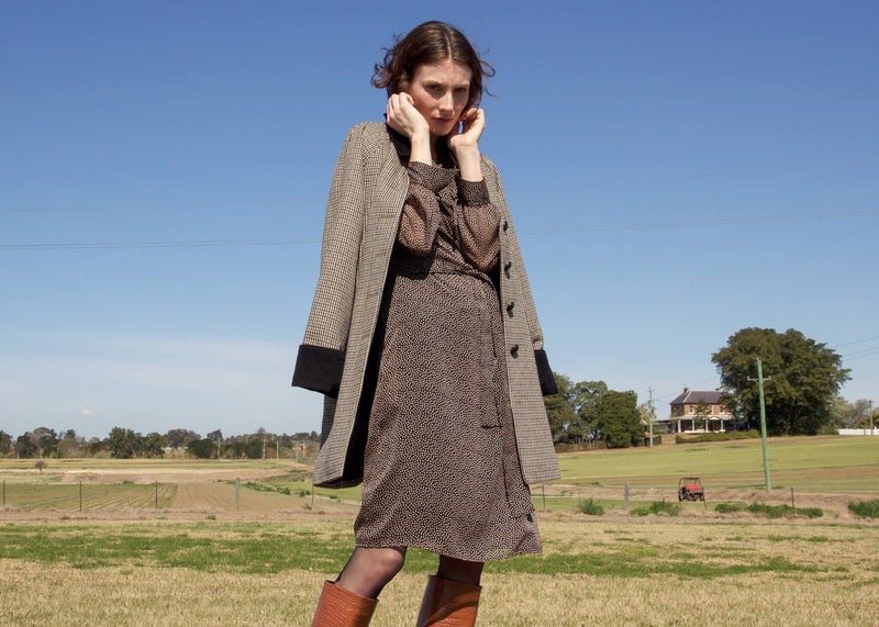 Olivia wears the Laila Chiffon Wrap Dress and a wool coat, both from Laundromat