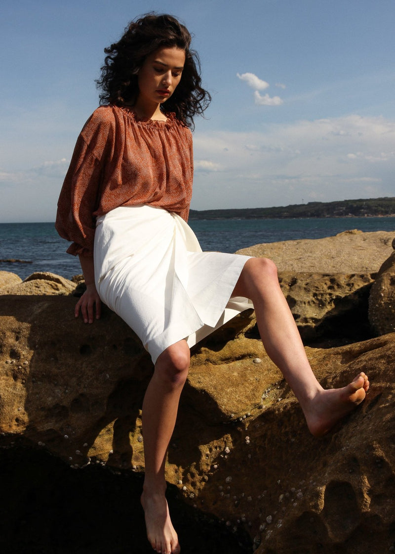 India sitting on a rock wearing the Anais Wrap Skirt in Vienna from Laundromat
