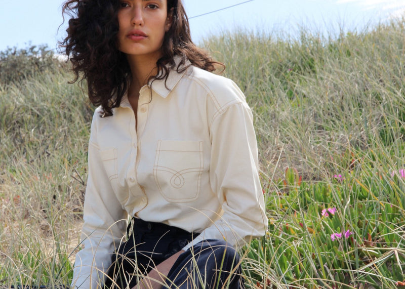 India sitting on a grassy hill wearing the Anouk Denim Shirt in Double Cream from Laundromat