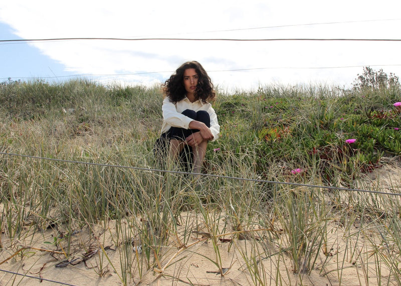 India sitting in a field wearing the Anouk Denim Shirt in Double Cream by Laundromat