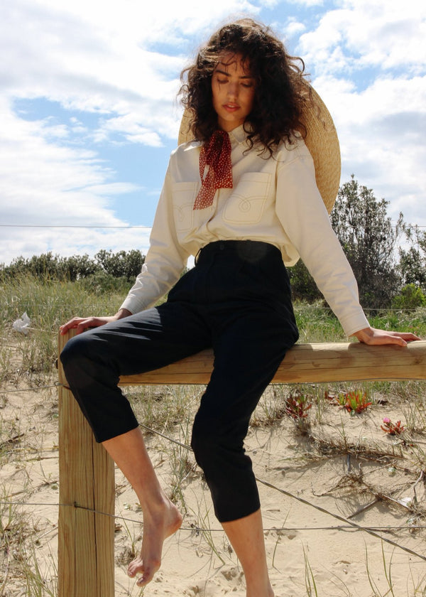 India sitting on a fence wearing the Anouk Denim Shirt in Double Cream with Elaine Pleat Trousers, both by Laundromat