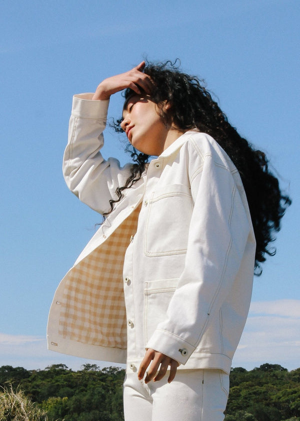 Marlo wears the Avalon Denim Chore Jacket in Double Cream with gingham lining from Laundromat