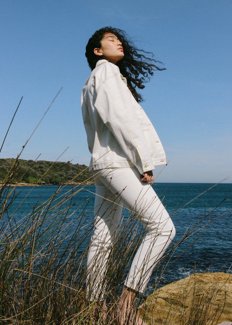 Marlo standing on a rock wearing the Avalon Denim Chore Jacket in Double Cream by Laundromat