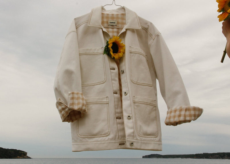 The Avalon Denim Chore Jacket in Double Cream with rolled up gingham-lined sleeves and sunflower by Laundromat