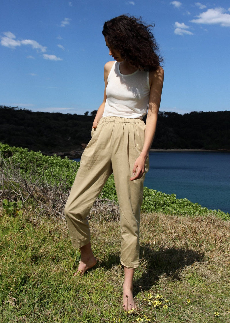 India on a grassy hill wearing the Cecil Singlet in Jasmine Front with beige trousers, both from Laundromat