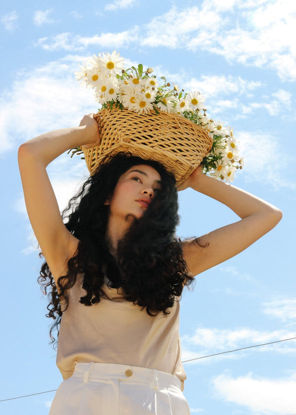 Marlo carrying a basket of marguerites above her head, wearing the Ceres Camisole in Biscotti by Laundromat