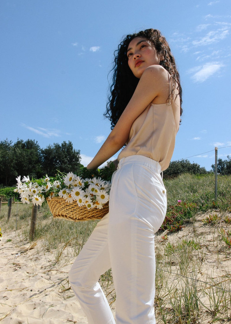 Marlo carrying a basket of flowers, wearing the Ceres Camisole in Biscotti with ivory trousers, both by Laundromat