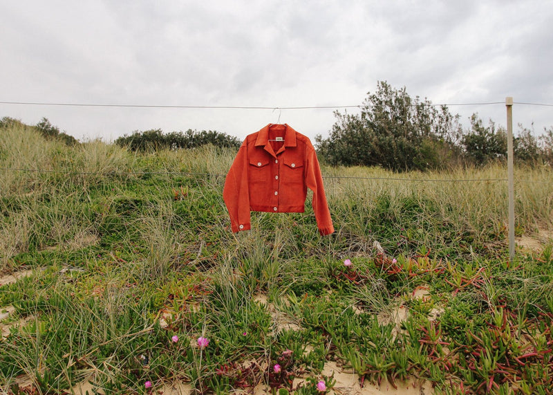 The Clementina Corduroy Jacket in Tangelo from Laundromat hanging on a wire fence in a field