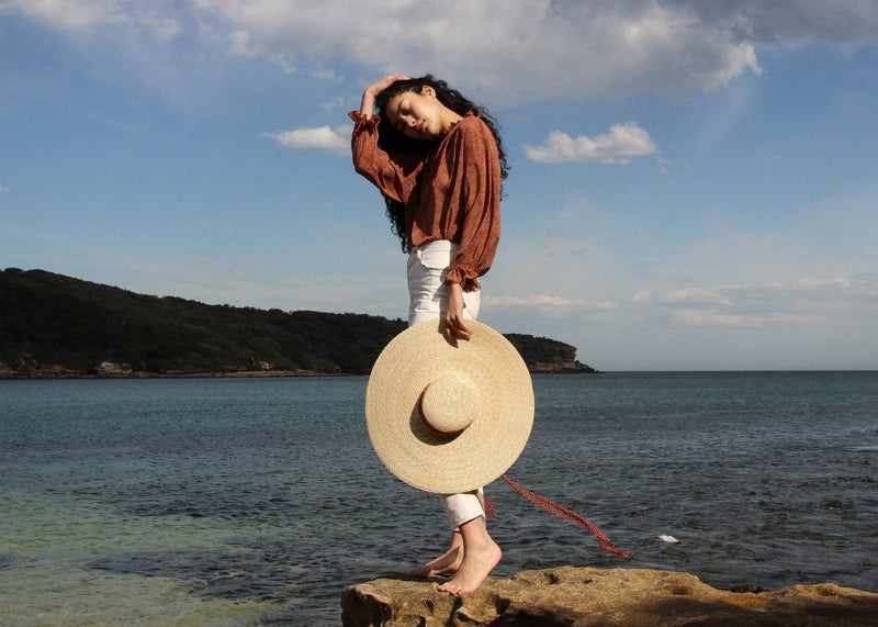 Marlo standing by the sea carrying the Clothilde Straw Boater Hat in Anise Dot Ribbon from Laundromat