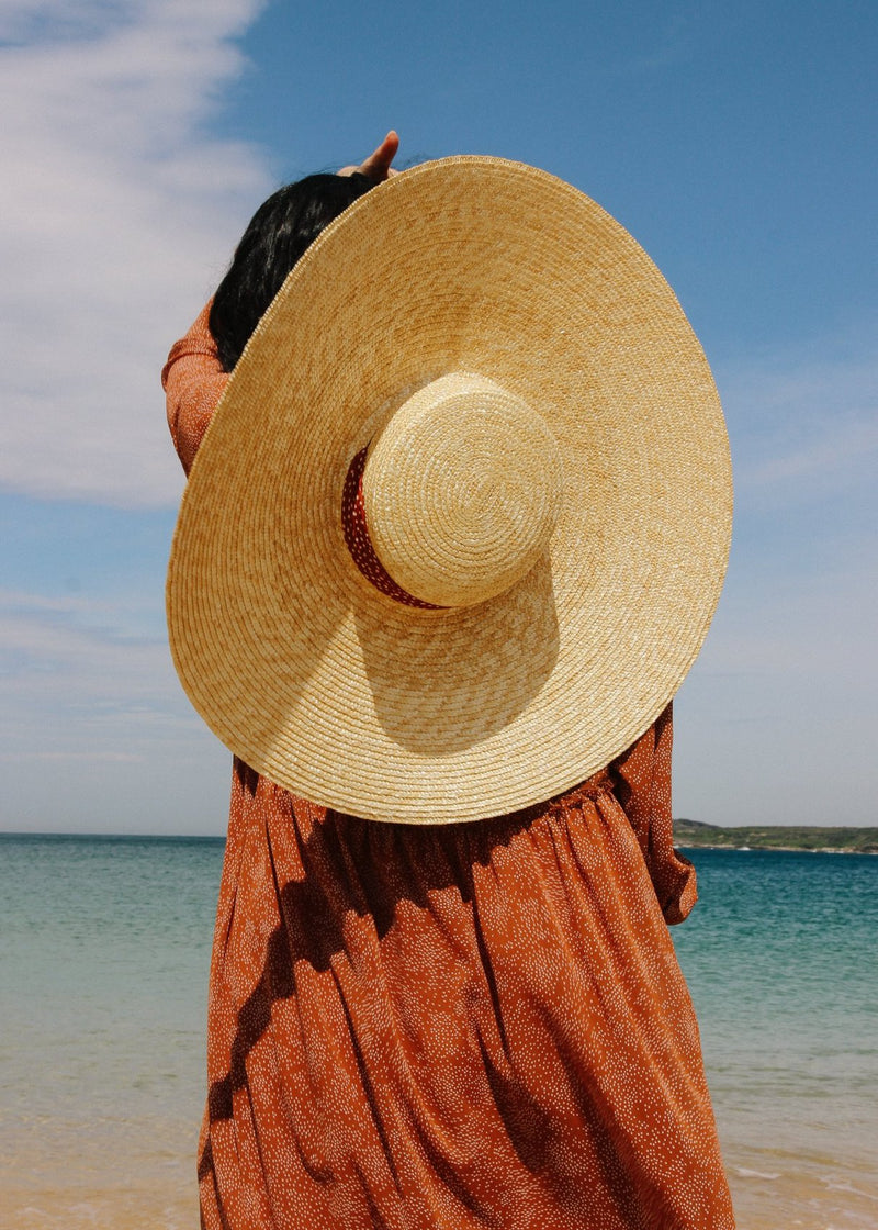 Back of Marlo wearing the Clothilde Straw Boater Hat in Anise Dot Ribbon from Laundromat