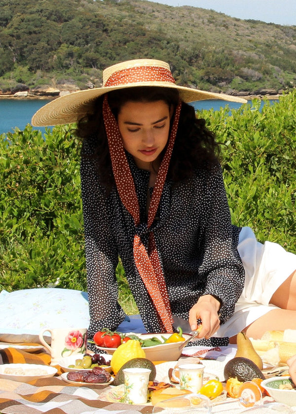 India picnicking in the Clothilde Straw Boater Hat in Anise Dot Ribbon and Carmen Blouse, both from Laundromat