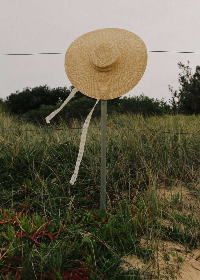 The Clothilde Straw Boater Hat in Seaside Daisy Lace from Laundromat on a fence post in a field