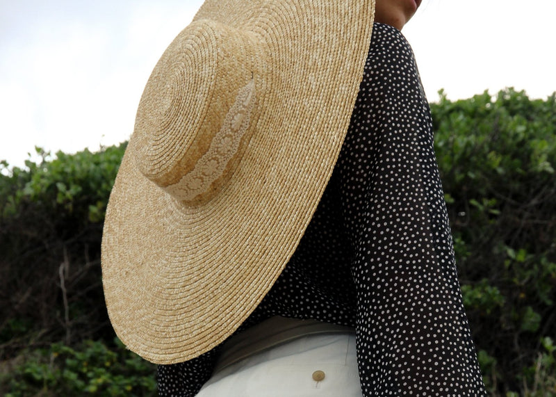 The Clothilde Straw Boater Hat in Seaside Daisy Lace from Laundromat, worn on the back