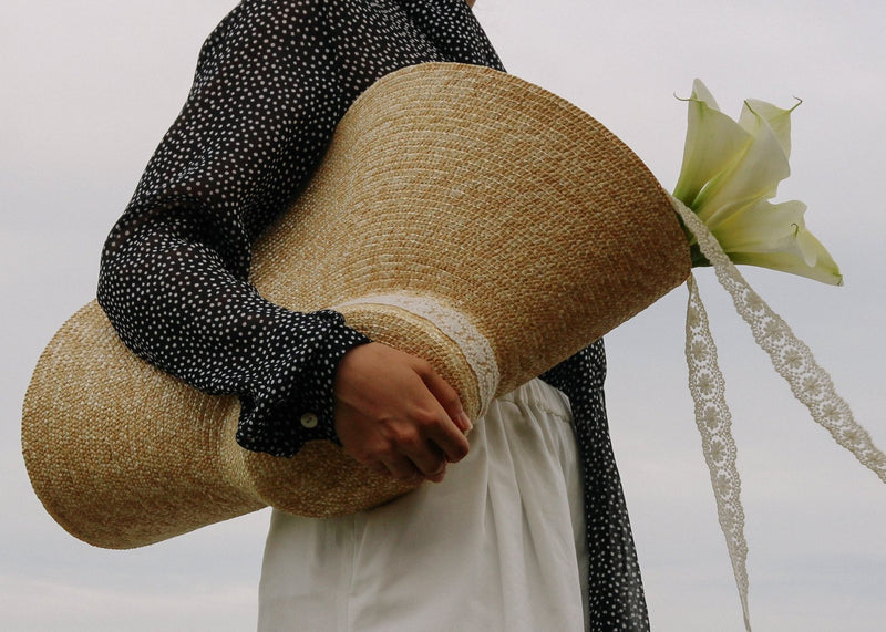 Model carrying white lilies in the Clothilde Straw Boater Hat in Seaside Daisy Lace from Laundromat