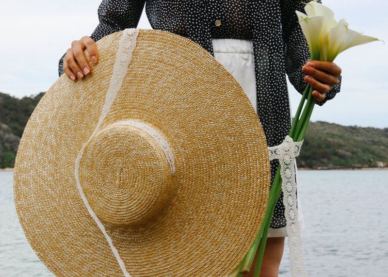 A model holding white lilies and the Clothilde Straw Boater Hat in Seaside Daisy Lace from Laundromat