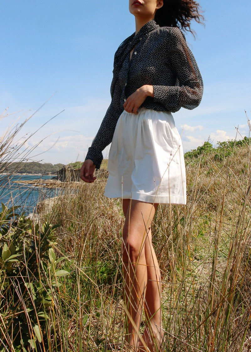 India on a hillside wearing the Cosette Shorts in Magnolia from Laundromat