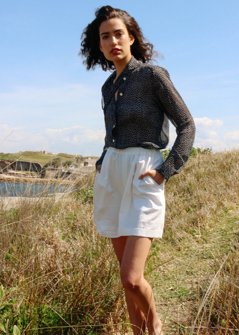 India on a grassy hill wearing the Cosette Shorts in Magnolia from Laundromat