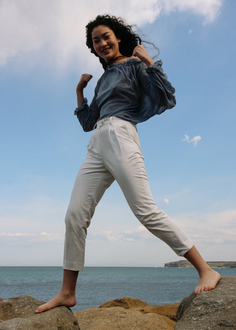 Marlo walking across two rocks in the Elaine Pleat Trousers in Alabaster from Laundromat