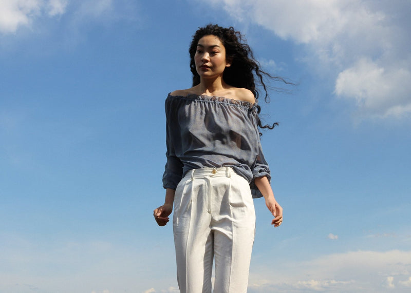 Marlo wearing the Elaine Pleat Trousers in Alabaster with blue blouse from Laundromat