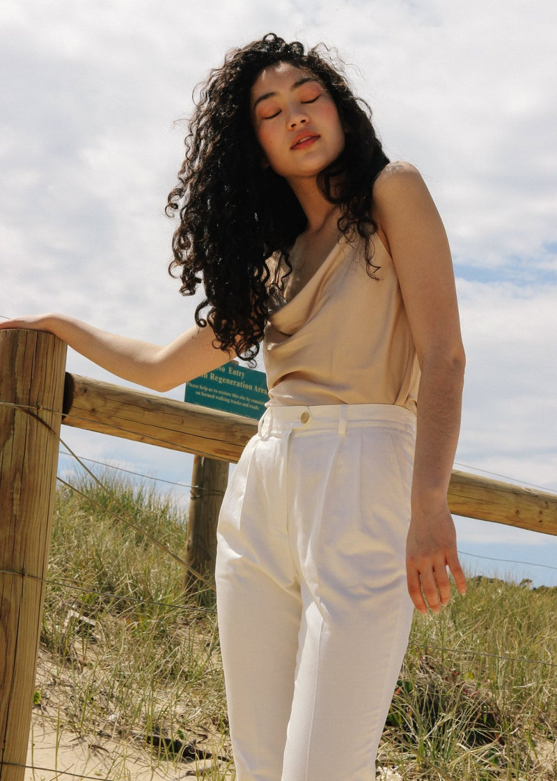 Marlo wears the Elaine Pleat Trousers in Alabaster with Ceres Camisole, both from Laundromat