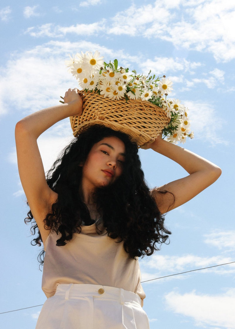 Marlo carrying a basket of marguerites above her head, wearing the Elaine Pleat Trousers in Alabaster from Laundromat