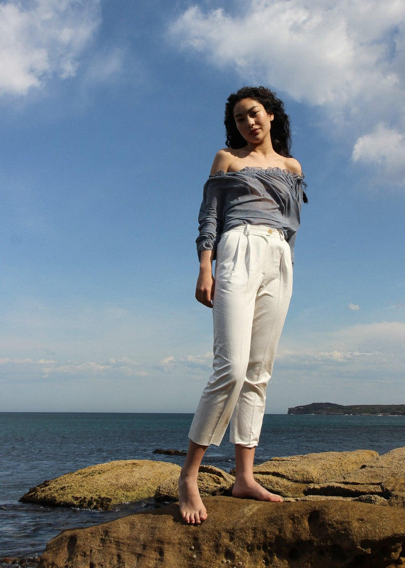 Marlo standing on a rock wearing the Elaine Pleat Trousers in Alabaster from Laundromat