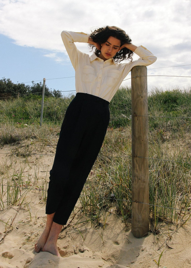 India leaning on a fence post wearing the Elaine Pleat Trousers in French Navy by Laundromat