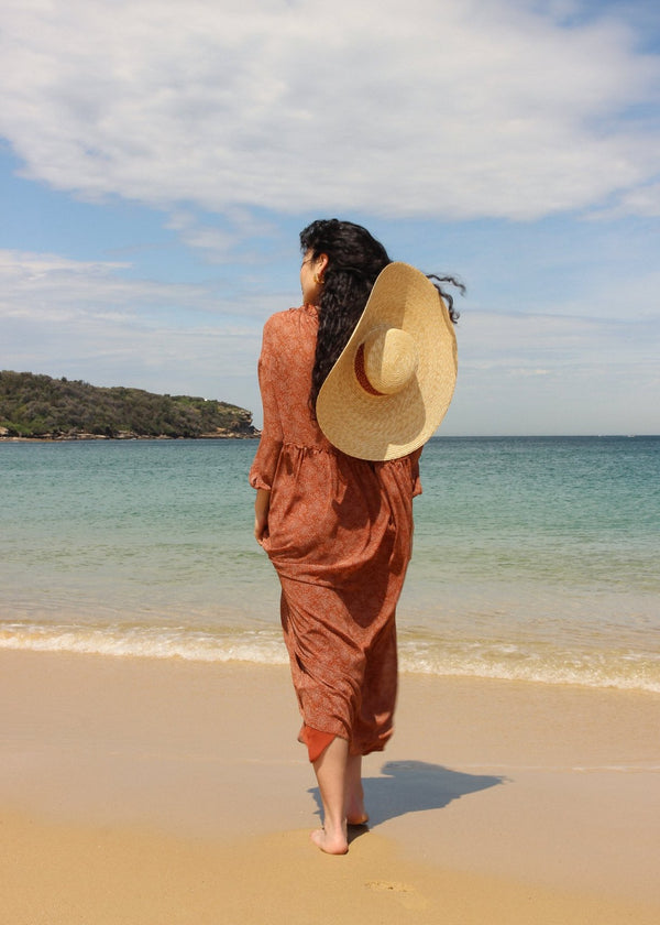 Marlo at the beach in the Emmeline Dress in Cinnamon Poppyseed with a straw hat on her back, both by Laundromat
