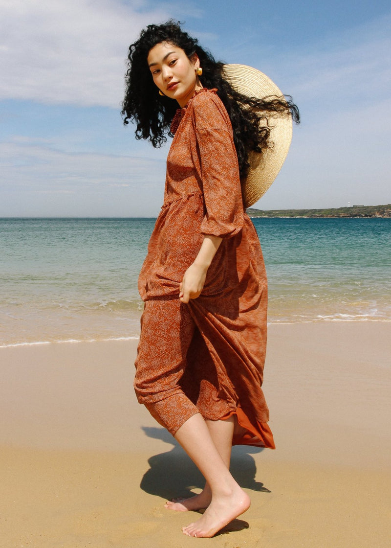 Marlo walking on the beach wearing the Emmeline Dress in Cinnamon Poppyseed print from Laundromat