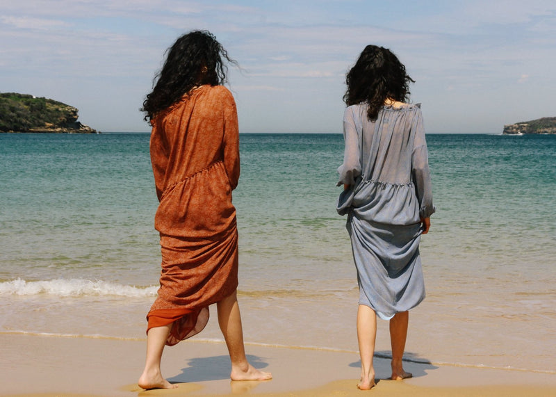 India and Marlo walking towards the ocean, both wearing the Emmeline Dress from Laundromat