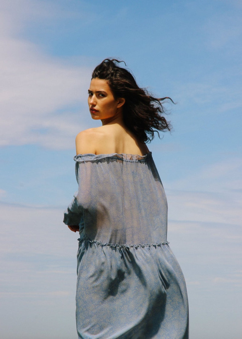Back of India wearing the Emmeline Dress in Cornflower Poppyseed off-the-shoulder by Laundromat