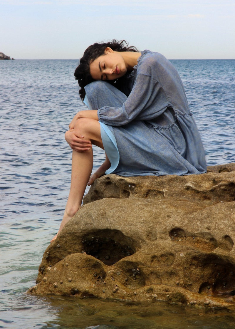 India sitting on a rock by the ocean, wearing the Emmeline Dress in Cornflower Poppyseed from Laundromat