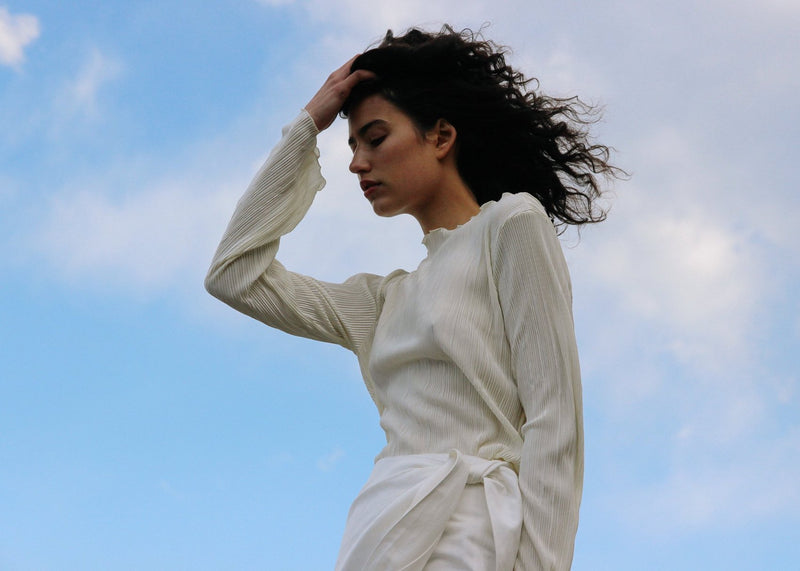 India wears the Grecia Plissé Top in Pearl with a white skirt, both from Laundromat