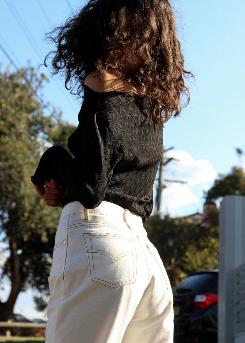 India wears the Helen Mom Jeans in Double Cream with Oriana Plissé Top, both by Laundromat