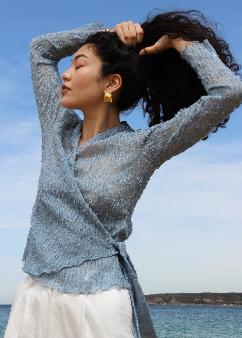 Marlo tying her hair in the Luela Fil Coupé-Plissé Wrap Top in Cornflower from Laundromat