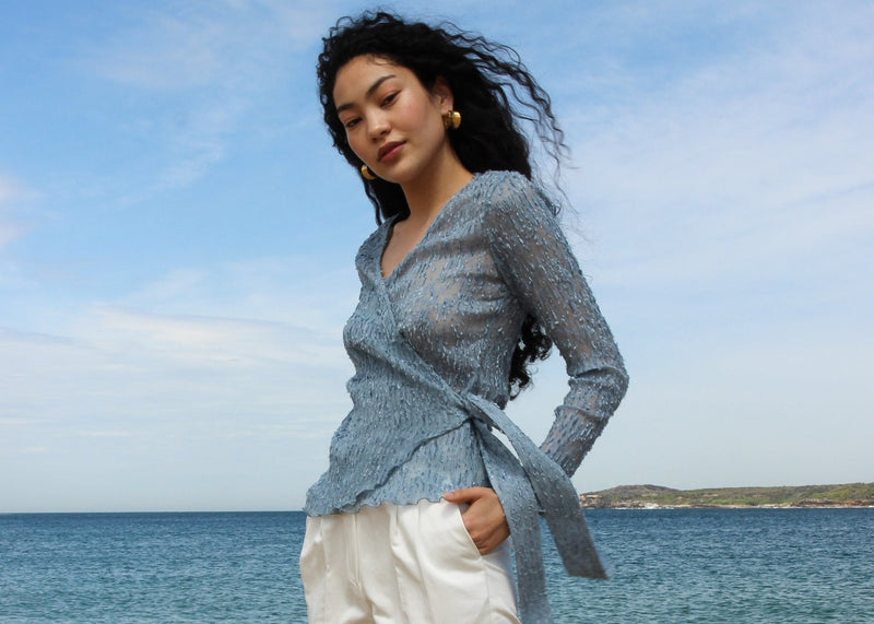 Marlo by the sea wearing the Luela Fil Coupé-Plissé Wrap Top in Cornflower from Laundromat