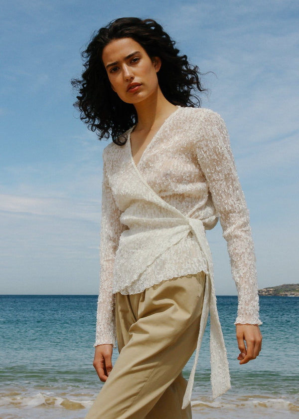 India wears the Luela Fil Coupé-Plissé Wrap Top in Vanilla from Laundromat