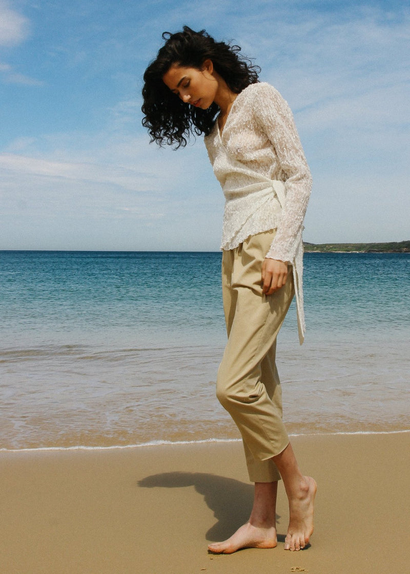 India wears the Luela Fil Coupé-Plissé Wrap Top in Vanilla and beige trousers, both from Laundromat
